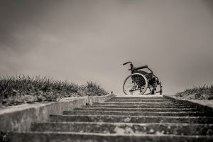 Rollstuhl vor einer Treppe, Symbolbild für Barrieren im Alltag