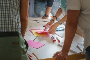 Mitarbeiterinnen und Mitarbeiter einer Kommunen tauschen sich über Zuständigkeiten für Bürgeranliegen aus. (Beispielfoto)
