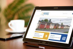 Wohnzimmer mit Tablet, auf dem die Online-Beteiligungsplattform friedberg-mitmachen.de sichtbar ist