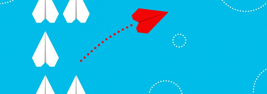 blaues Foto mit 5 weißen Papierfliegern und einem roten Flieger, der einen anderen Weg einschlägt. Symbolbild fürs Umdenken.