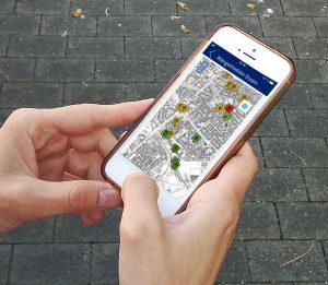 Hände mit Smartphone. Auf dem Bildschirm des Handys ist die App vom Mängelmelder Essen zu sehen.